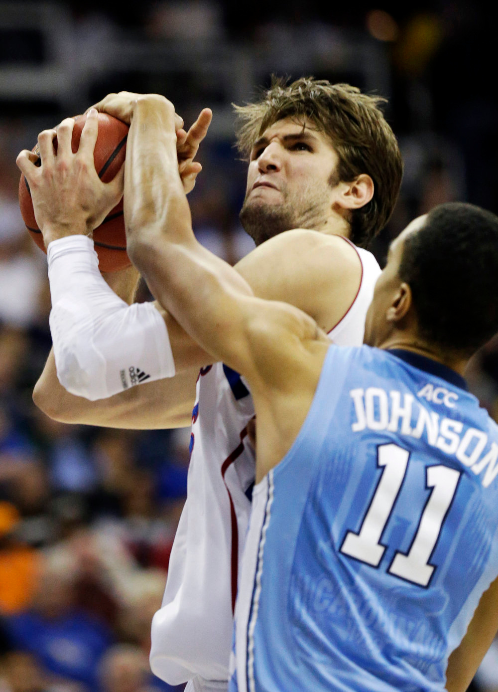 . Kansas center Jeff Withey, rear, is fouled by North Carolina forward Brice Johnson (11) during the first half of a third-round game in the NCAA college basketball tournament at the Sprint Center in Kansas City, Mo., Sunday, March 24, 2013. (AP Photo/Orlin Wagner)