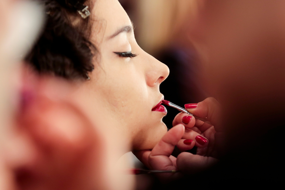 . A model gets her lips prepared prior to the presentation of Lena Hoschek\'s Autumn Winter 2014 collection during the Mercedes Benz Fashion Week in Berlin, Tuesday, Jan. 14, 2014. (AP Photo/Markus Schreiber)