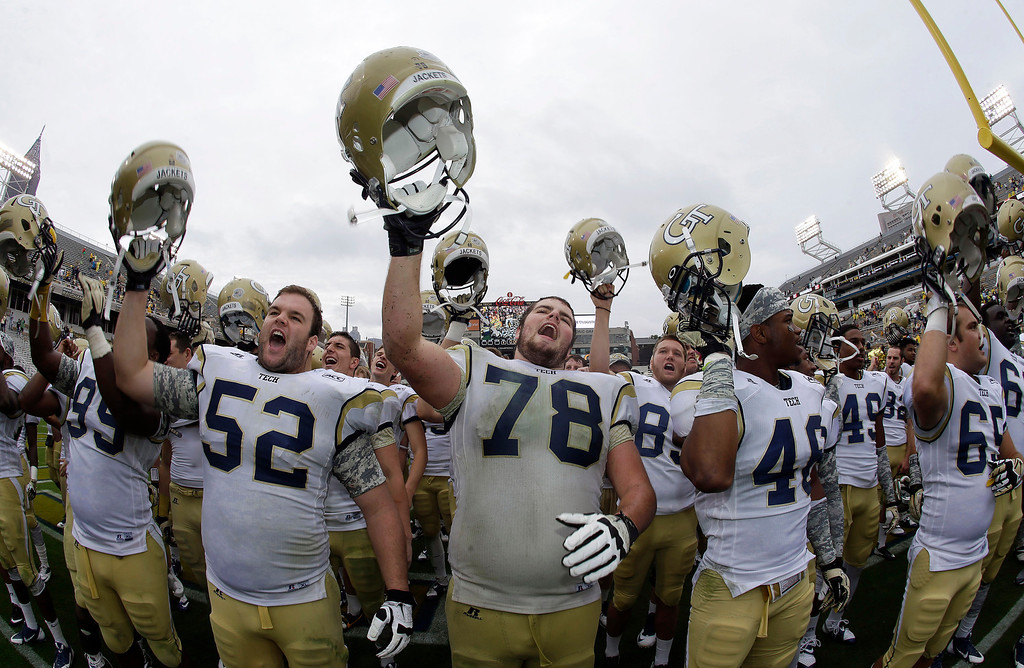 . Georgia Tech\'s Trey Braun (78) and Will Jackson (52) and Tremayne McNair (46) celebrate after an NCAA college football game against the Syracuse Saturday, Oct. 19, 2013, in Atlanta. Tech won 56-0. (AP Photo/John Bazemore)