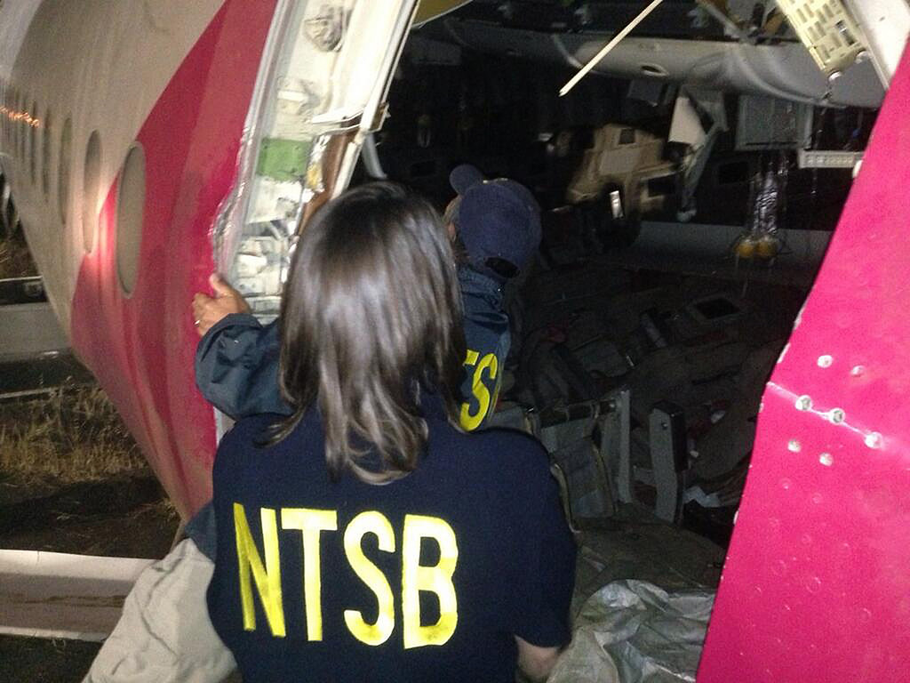 . This handout photo provided July 7, 2013 by the National Transportation Safety Board shows NTSB Chairwoman Deborah A.P. Hersman and Investigator-in-Charge Bill English looking at interior damage to Asiana Flight 214 during their first site assessment in San Francisco, Calif. US officials were combing through the wreckage of an Asiana Airlines Boeing 777 passenger jet in San Francisco Sunday, as they tried to determine why it crashed onto the runway July 6, killing two people and injuring 182 others. The crash sheared off the plane\'s landing gear and tore the tail off the fuselage. Large portions of the plane\'s body were burned out in the fire that then erupted. Hersman said much of the destruction isn\'t visible in the pictures and footage shown in the news.  (NTSB via AFP/Getty Images)