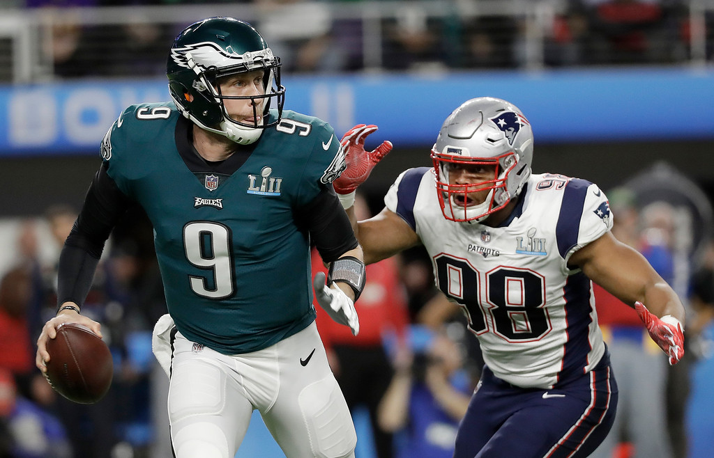 . Philadelphia Eagles\' Nick Foles (9) scrambles from New England Patriots\' Trey Flowers during the first half of the NFL Super Bowl 52 football game Sunday, Feb. 4, 2018, in Minneapolis. (AP Photo/Mark Humphrey)