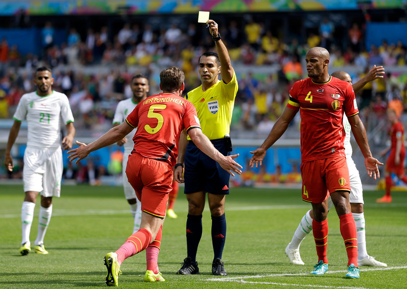 . Referee Marco Rodriguez from Mexico gives a yellow card to Belgium\'s Jan Vertonghen as Vincent Kompany looks on at right, during the group H World Cup soccer match between Belgium and Algeria at the Mineirao Stadium in Belo Horizonte, Brazil, Tuesday, June 17, 2014.  (AP Photo/Ricardo Mazalan)