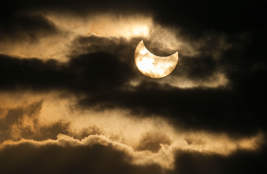 . A partial solar eclipse is seen in a break in the clouds during rush hour in downtown Wichita Kan., Thursday, Oct. 23, 2014. (AP Photo/The Wichita Eagle, Travis Heying)