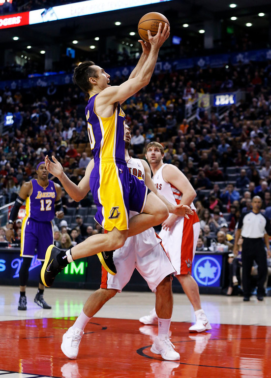 . Los Angeles Lakers\'  Steve Nash goes to the net past Toronto Raptors\' Jose Calderon (back) during the first half of their NBA basketball game in Toronto, January 20, 2013.     REUTERS/Mark Blinch