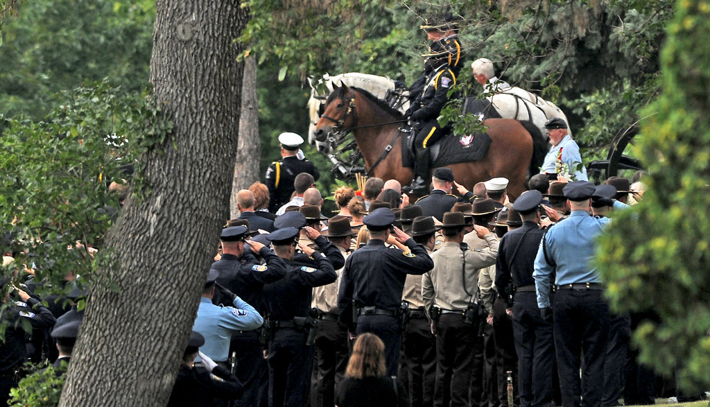 . Police officers salute as a caisson carrying Scott Patrick\'s casket approaches the burial area at Acacia Park Cemetery.  (Pioneer Press: Jean Pieri)