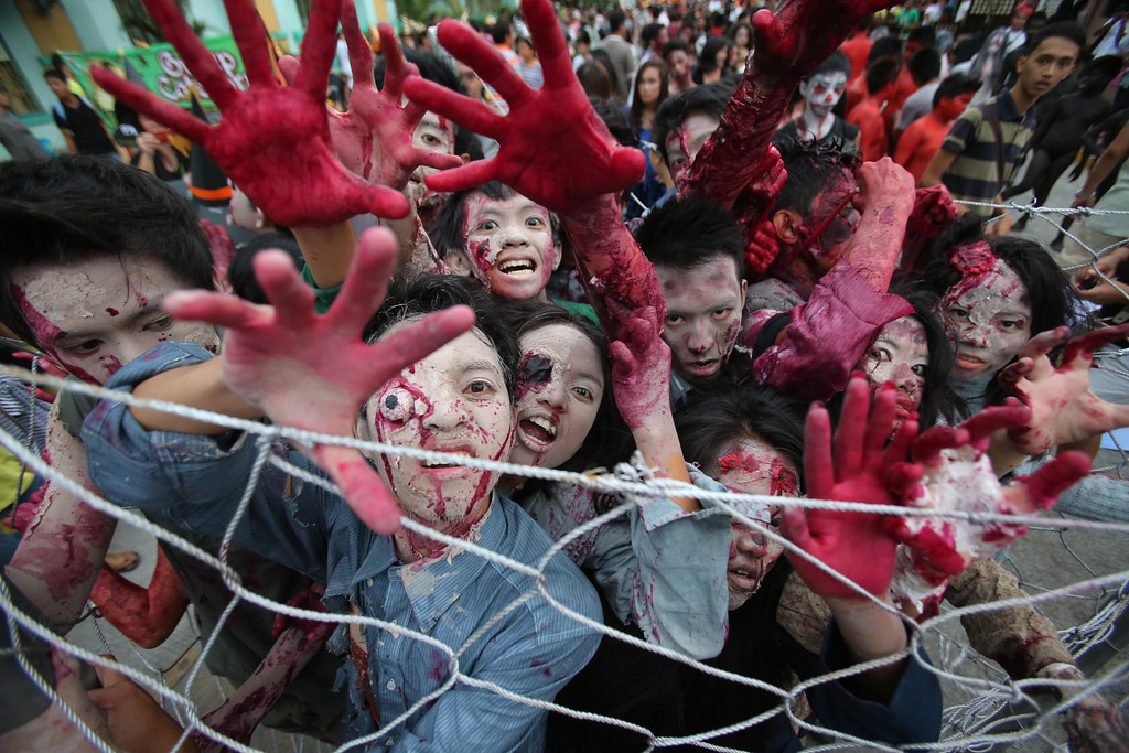 . Filipinos wearing zombie costumes act during  a Halloween Parade in Marikina city, east of Manila, Philippines on Wednesday, Oct. 30, 2013. Hundreds of residents and government employees joined the parade as the country prepares to observe All Saints Day on Nov. 1. (AP Photo/Aaron Favila)