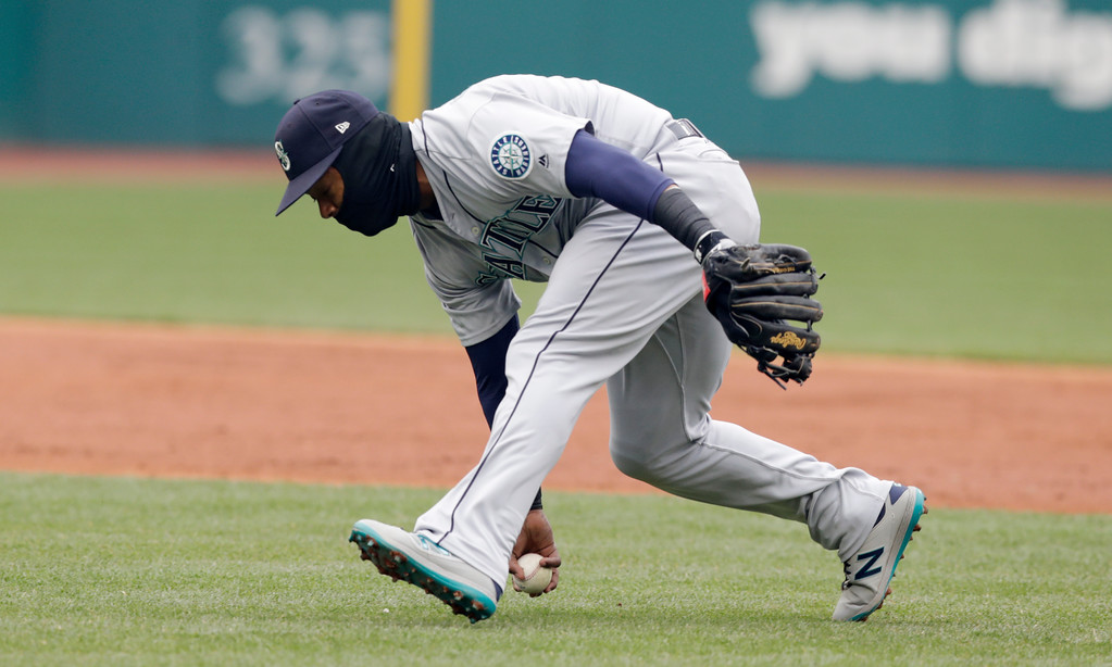 . Seattle Mariners\' Jean Segura barehands a ball hit by Cleveland Indians\' Tyler Naquin in the second inning of a baseball game, Saturday, April 28, 2018, in Cleveland. Naquin was safe at first base. Edwin Encarnacion scored on the play. (AP Photo/Tony Dejak)