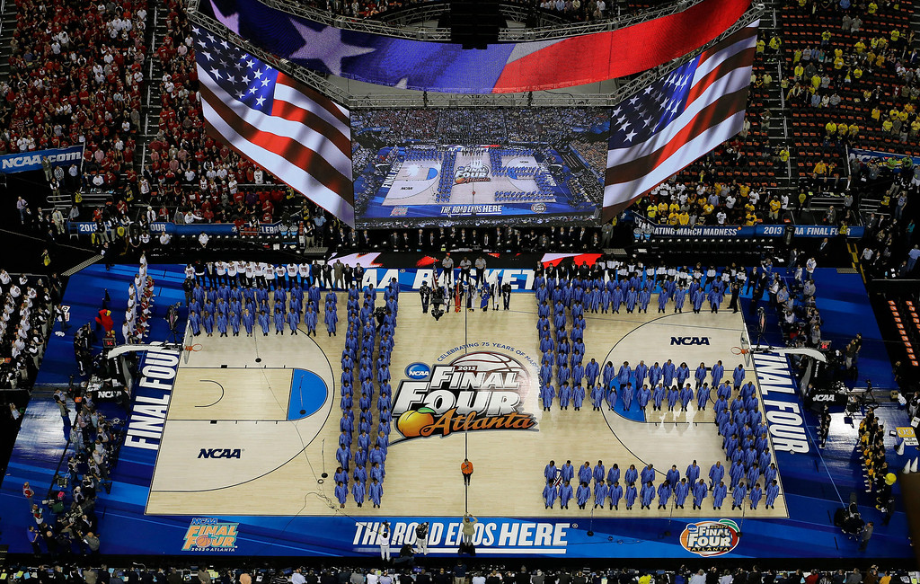 . The National Anthem is performed as a chorus forms a 75 for the 75th anniversary of the Final Four before the first half of the NCAA Final Four tournament college basketball semifinal game between Louisville and Wichita State Saturday, April 6, 2013, in Atlanta. (AP Photo/David J. Phillip)