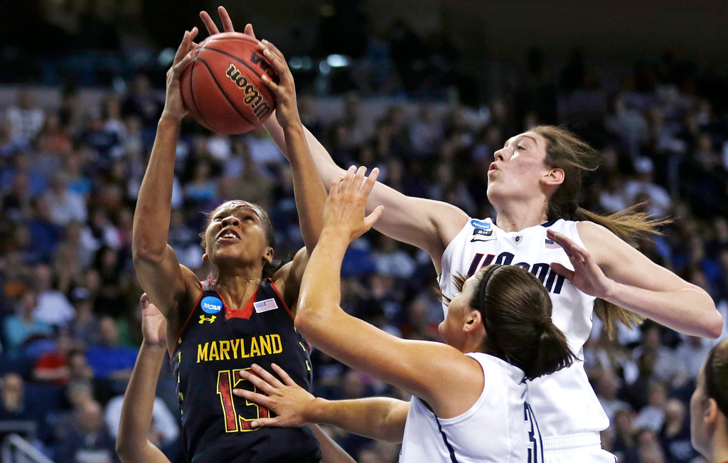 . Connecticut forward Breanna Stewart, right, tries to block a shot by Maryland center Alicia DeVaughn (13) during the first half of an NCAA women\'s college regional semifinal basketball game in Bridgeport, Conn., Saturday, March 30, 2013. At bottom right is Connecticut center Stefanie Dolson. (AP Photo/Charles Krupa)
