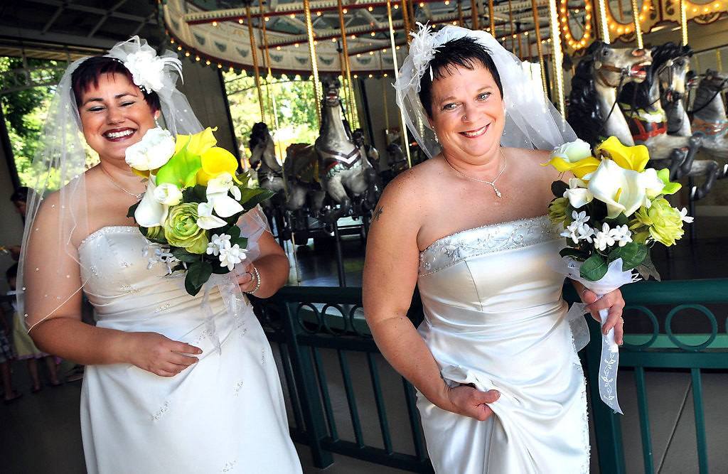 ". Rochelle ""Shay\"" Imdieke, left, and Shirley Otto leave the carousel at Como Park after getting wedding photos taken before they were married at Excedra Garden on Thursday, Aug. 1, 2013. (Pioneer Press: Jean Pieri)"