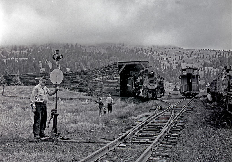 "September 1964. Cumbres turns were often accompanied by a fair number of photographers and just curious tourists, and for the crews it was almost like a public performance. The brakeman smiles for my camera as a family watches one of the engines, while two more photographers do their thing on the right.  Retired Alamosa railroader Woody Woodward wrote me, ""The brakeman by the switchstand is George Andriko. He was probably the conductor on that trip. He was around so long I think he gave Casey Jones his student trips. When I was in the 1st grade his wife was the Principal of the school and George was the 'old head' when I started on the RR at Alamosa in 1967. He started as a newspaper boy on the trains when he was about 15. His trainman date was around 1917 if I recall correctly."" Jimmy Blouch, another retired Rio Grande employee followed up with, ""Conductor seniority roster for July 1, 1966 shows: 1. Andriko, G. J. Date entered: 10-12-16 Date promoted: 12-22-22"". So we're looking at a trainman with 48 years of experience under his hat. Here is a guy who is number one on the Alamosa trainman's seniority list. He could hold any job in the district that he wanted. Most of the senior guys at Alamosa worked the standard gauge where they didn't have to deal with the cranky old narrow gauge equipment, long hours over slow track, damn steam engines, and so on. But interestingly George apparently must have liked the narrow gauge and its old fashioned ways. I'm sure George never would have thought of himself as a railfan, but...  Thanks Woody and Jimmy. Information like that brings an image to life."