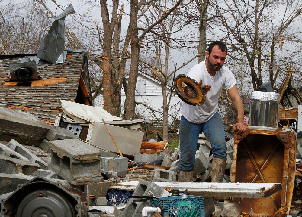 Description of . Justin Chandler searches through debris of his brother-n-law's shop after a storm ripped through Coble, Tenn. early Wednesday, Jan. 30, 2013. A large storm system packing high winds, hail and at least one tornado tore across a wide swath of the South and Midwest on Wednesday, killing one person, blacking out power to thousands and damaging homes. (AP Photo/Butch Dill)