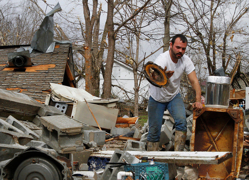 . Justin Chandler searches through debris of his brother-n-law\'s shop after a storm ripped through Coble, Tenn. early Wednesday, Jan. 30, 2013. A large storm system packing high winds, hail and at least one tornado tore across a wide swath of the South and Midwest on Wednesday, killing one person, blacking out power to thousands and damaging homes. (AP Photo/Butch Dill)