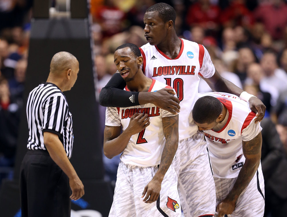 Description of . (L-R) Russ Smith #2, Gorgui Dieng #10 and Chane Behanan #21 of the Louisville Cardinals react after Kevin Ware #5 suffered a compound fracture to his leg in the first half against the Duke Blue Devils during the Midwest Regional Final round of the 2013 NCAA Men's Basketball Tournament at Lucas Oil Stadium on March 31, 2013 in Indianapolis, Indiana.  (Photo by Andy Lyons/Getty Images)