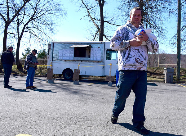 3/18/2020 Mike Orazzi | Staff Customer Matt Ryan after getting luck at a food truck on Middle Street in Bristol on Wednesday. Steve Lavoie, operator of the Top Dog food truck on Middle Street has made changes to how he servers customers because of the Coronavirus.