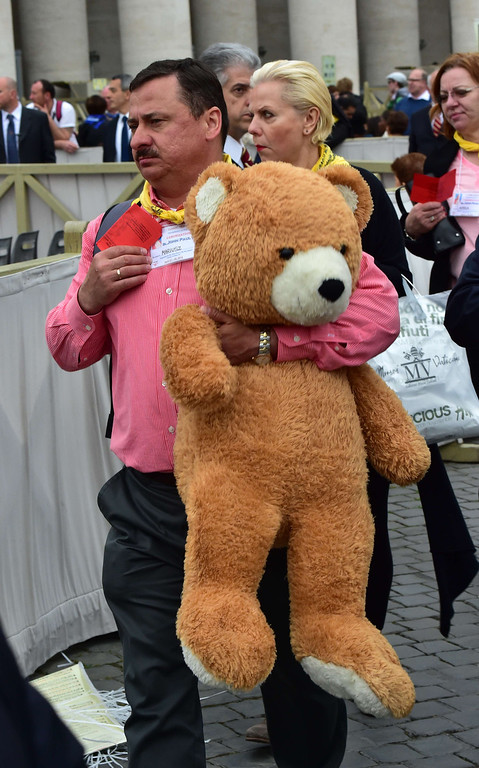 . A man carries a teddy bear as he arrive for the canonisation mass of Popes John XXIII and John Paul II on St Peter\'s at the Vatican on April 27, 2014. Catholics from around the world gathered in Rome on Sunday for a mass presided by Pope Francis to confer sainthood on John Paul II and John XXIII -- two influential popes who helped shape 20th century history.    AFP PHOTO / GIUSEPPE CACACE