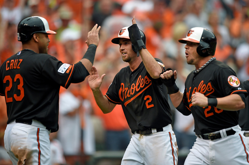 . Baltimore Orioles\' Nelson Cruz, from left, J.J. Hardy and Steve Pearce celebrate after scoring on a double by Delmon Young in the eighth inning of Game 2 in baseball\'s AL Division Series against the Detroit Tigers in Baltimore, Friday, Oct. 3, 2014. Baltimore won 7-6.  (AP Photo/Nick Wass)