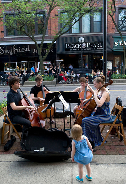 17-month-old Eloise Richardson of Ann Arbor watches the Pique Cello Quartet perform pop arrangements on Main Street in Ann Arbor, MI on May 3, 2012.  The group, made up of University of Michigan students, from left, are Jamie Davis, Dan Smith, Corie Lint, and Pia Eva Greiner.  (Photo by Mark Bialek)
