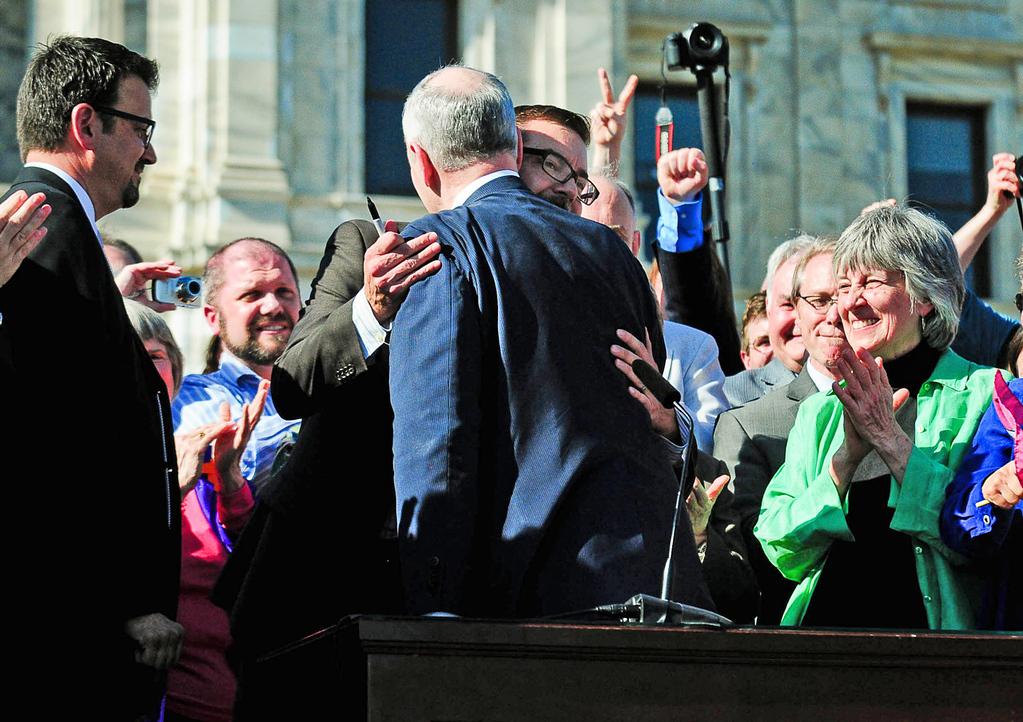 . Gov. Mark Dayton hugs Sen. Scott Dibble, DFL-Minneapolis, after signing the same-sex marriage bill. At right is Rep. Karen Clark, DFL-Minneapolis.  (Pioneer Press: Ben Garvin)