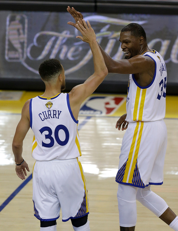 . Golden State Warriors guard Stephen Curry (30) and forward Kevin Durant react after scoring against the Cleveland Cavaliers during the first half of Game 1 of basketball\'s NBA Finals in Oakland, Calif., Thursday, June 1, 2017. (AP Photo/Ben Margot)