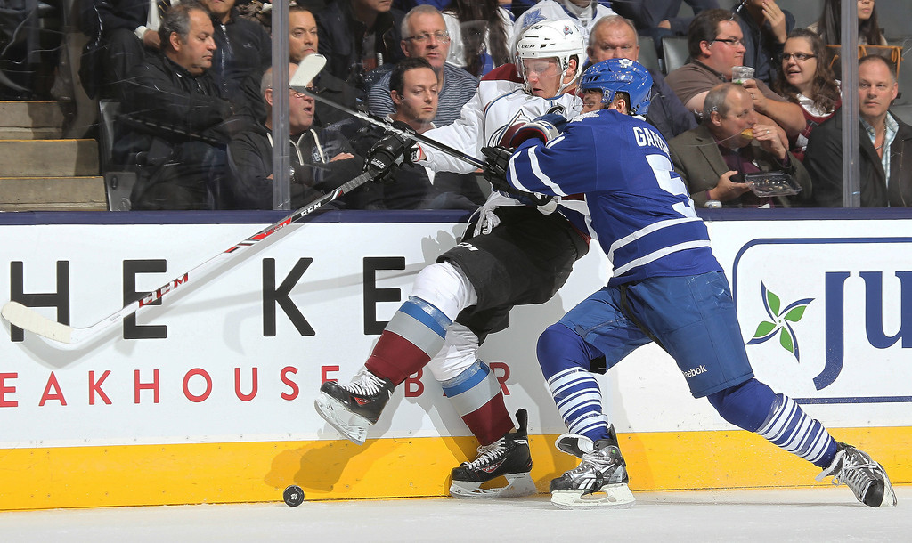 . Gabriel Landeskog #92 of the Colorado Avalanche is squeezed into the boards by Jake Gardiner #51 of the Toronto Maple Leafs during an NHL game at the Air Canada Centre on October 8, 2013 in Toronto, Ontario, Canada. (Photo by Claus Andersen/Getty Images)