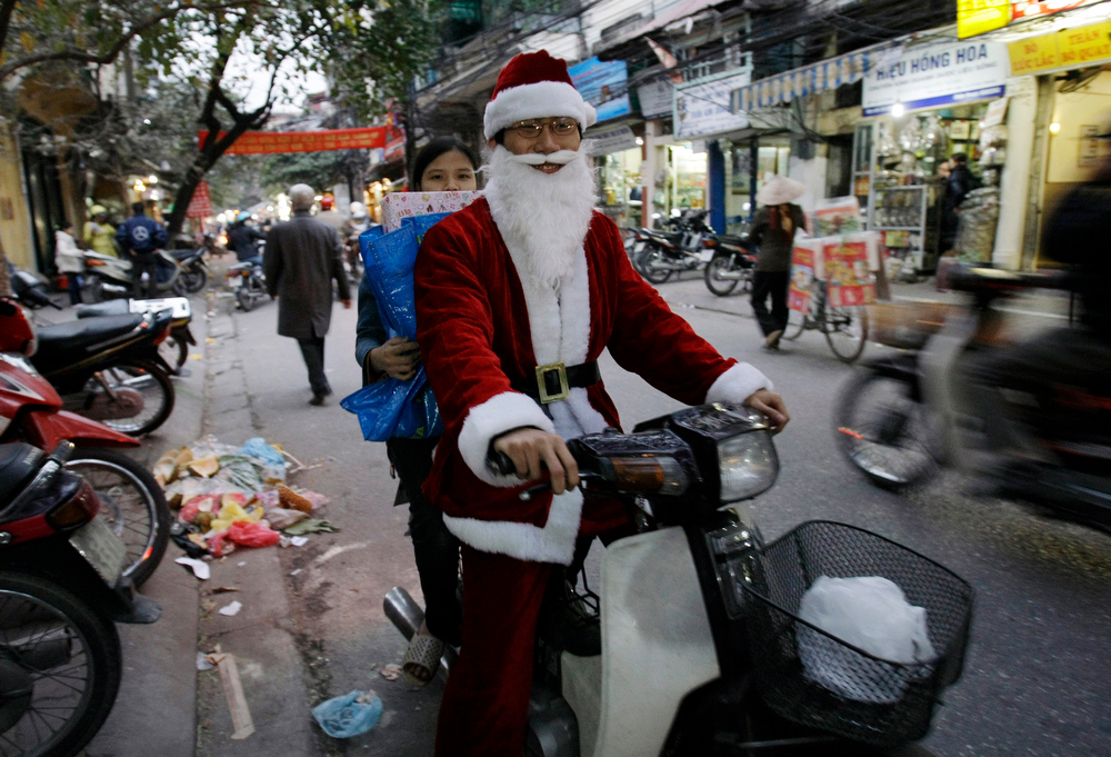 Description of . A delivery person drives a motorcycle wearing Santa Claus costume in Old Quarter neighborhood in Hanoi, Vietnam, Tuesday, Dec. 23, 2008. Vietnam has about 6 million Catholics, the second largest in Southeast Asia after the Philippines. Santa Claus and Christmas trees are popular in Vietnam. (AP Photo/Chitose Suzuki)