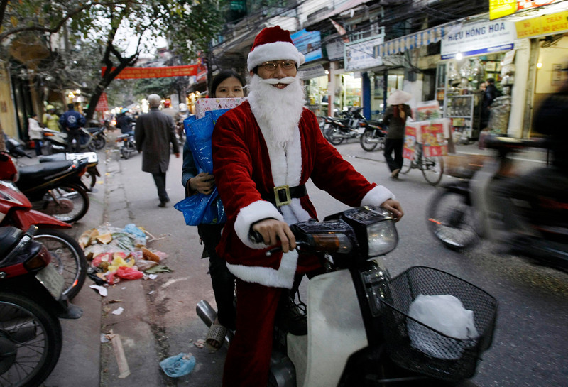 . A delivery person drives a motorcycle wearing Santa Claus costume in Old Quarter neighborhood in Hanoi, Vietnam, Tuesday, Dec. 23, 2008. Vietnam has about 6 million Catholics, the second largest in Southeast Asia after the Philippines. Santa Claus and Christmas trees are popular in Vietnam. (AP Photo/Chitose Suzuki)