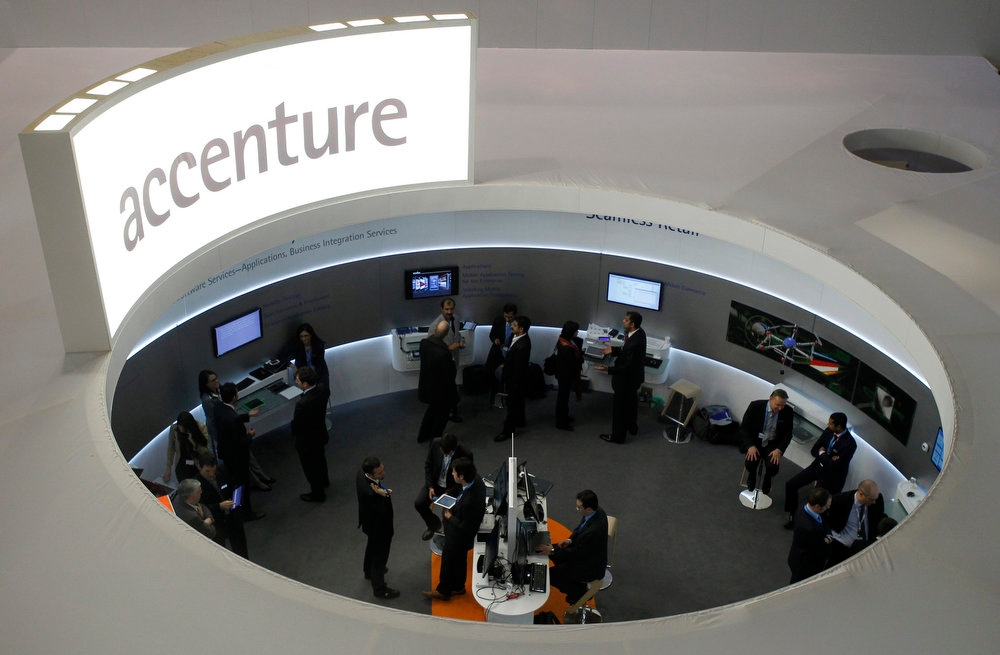 . Visitors look at devices at the Accenture stand at the Mobile World Congress in Barcelona on February 26, 2013. The GSMA Mobile World Congress, representing the interests of the worldwide mobile communications industry, will take place from February 25 to 28 in Barcelona.  REUTERS/Albert Gea