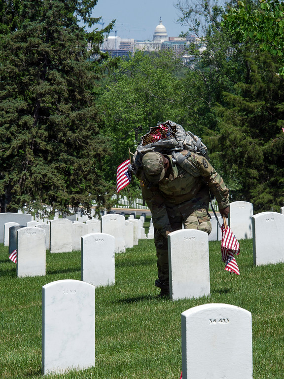 . With the U.S. Capitol in the background, a member of the Army 3d U.S. Infantry Regiment, The Old Guard, places a glag at the headstone of fallen military members during its annual Flags In ceremony at Arlington National Cemetery,  Thursday, May 24, 2018, in Arlington, Va. (AP Photo/Cliff Owen)