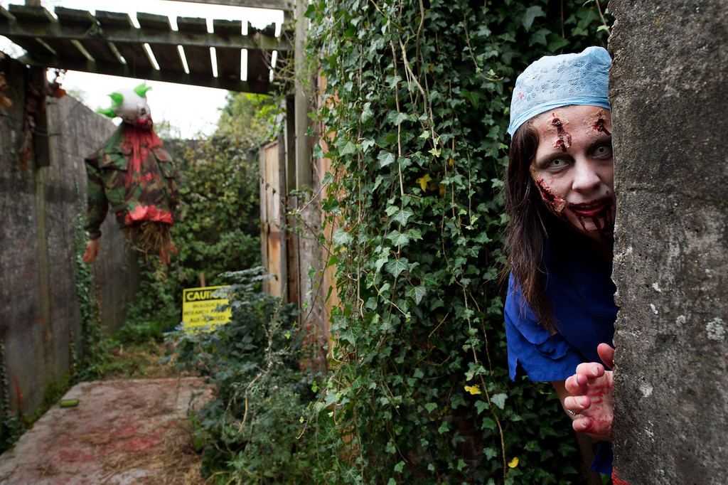 """. A volunteer \""""zombie\"""" poses for a picture as she waits for participants during one of Britain\'s biggest horror events, the \""""Zombie Evacuation Race\"""" at Carver Barracks near Saffron Walden, England, on October 5, 2013. The race sees thousands of participants attempt to complete a gruelling 5 kilometre cross-country run, while evading \""""zombies\"""", intent on snatching the three life-line strips hanging from every runner\'s waist.  Those who manage to get through with any strips remaining are named as survivors while those without take home an \""""infected\"""" badge.  LEON NEAL/AFP/Getty Images"""