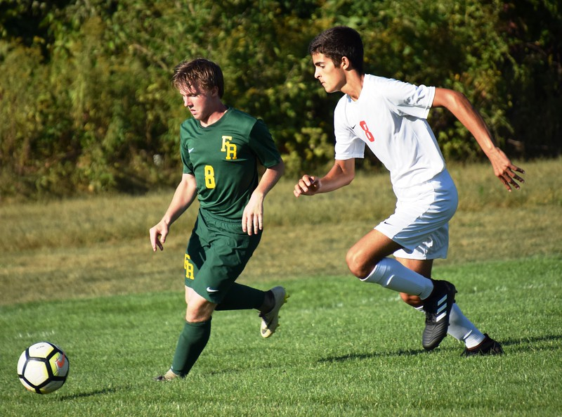 Andrew Jamison of host Flat Rock (right) is pursued by Remington Emelian of New Boston Huron during Monday's Huron League matchup. The Rams went on to suffer a 5-0 defeat against the second-place Chiefs. Alex Muller - For Digital First Media