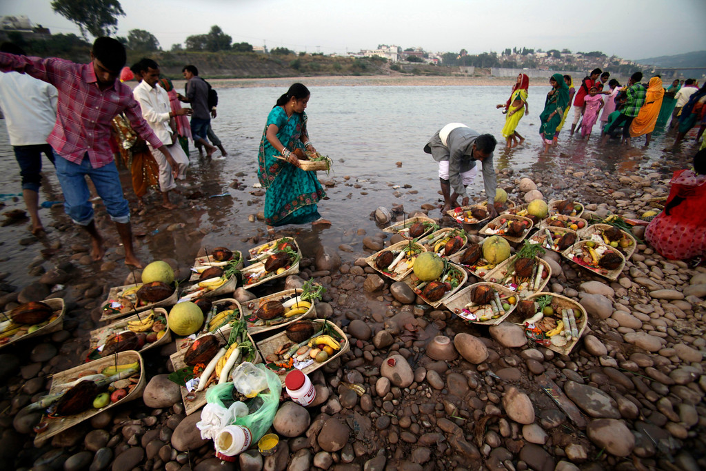 . Hindu devotees prepare ritualistic offerings before praying to the Sun God on the banks of the Tawi River during Chhath Puja festival in Jammu, India, Friday, Nov. 8, 2013.  (AP Photo/Channi Anand)