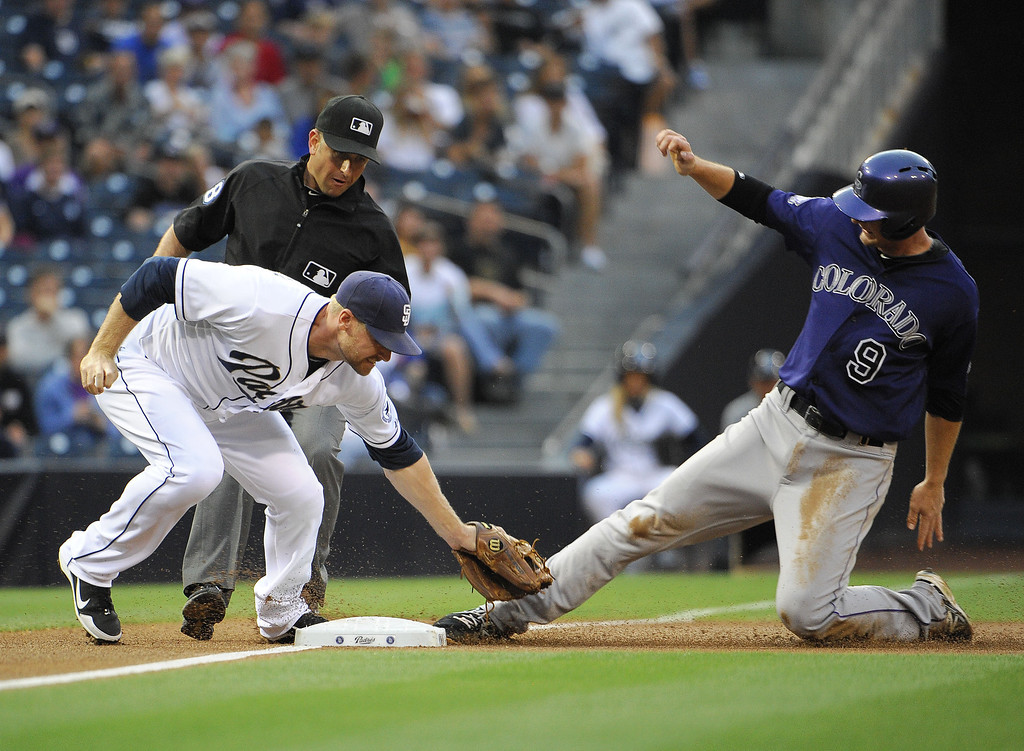 . DJ LeMahieu #9 of the Colorado Rockies is tagged out by Chase Headley #7 of the San Diego Padres as he tries to steal third base during the first inning of a baseball game at Petco Park on July 10, 2013 in San Diego, California.  (Photo by Denis Poroy/Getty Images)