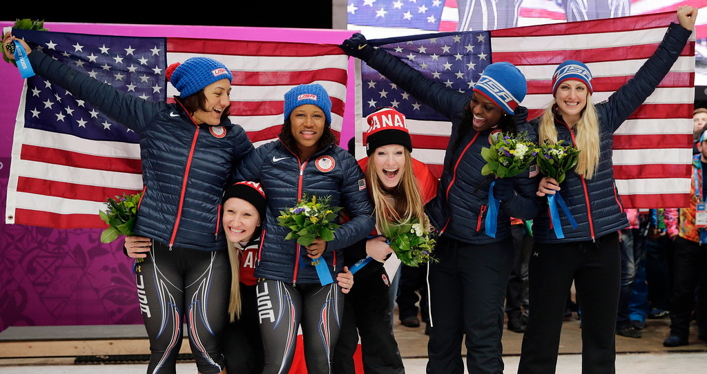 . Gold medal winners from Canada Kaillie Humphries and Heather Moyse, poke their heads under the flag as silver medal winners from the United States Elana Meyers and Lauryn Williams, and bronze medal winners from the United States Jamie Greubel and Aja Evans pose for pictures after the women\'s bobsled competition at the 2014 Winter Olympics, Wednesday, Feb. 19, 2014, in Krasnaya Polyana, Russia. (AP Photo/Jae C. Hong)