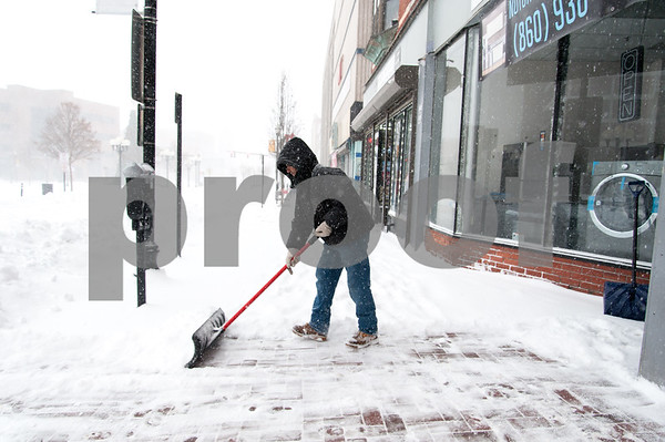 01/04/18 Wesley Bunnell | Staff A blizzard featuring high winds and causing icy conditions hit CT throughout the day on Thursday. Osvaldo Aguvo shovels snow in front of apartments near Central Park.