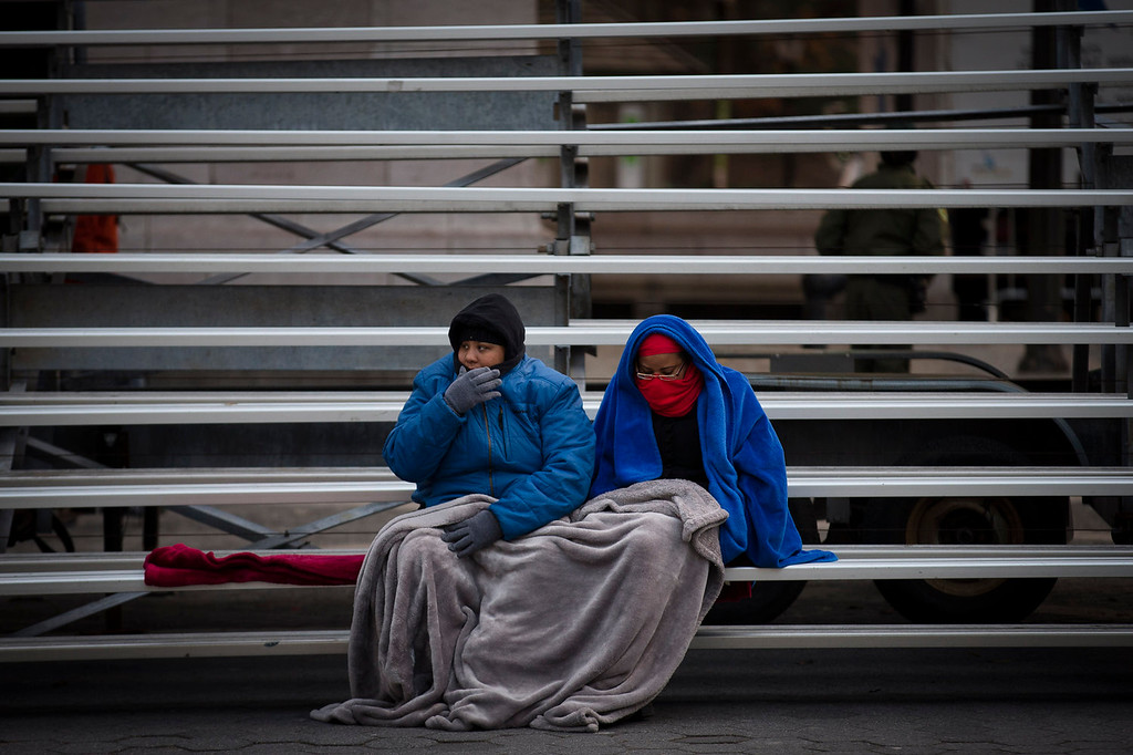 . Crystal Nix, left, and Destiny Golden brave the cold while sitting on bleachers as they wait for the 87th Annual Macy\'s Thanksgiving Day Parade, Thursday, Nov. 28, 2013, in New York. (AP Photo/John Minchillo)