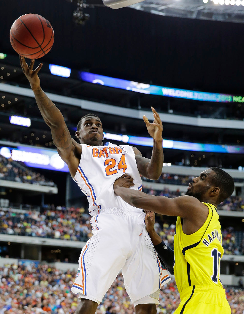 Description of . Florida\'s Casey Prather (24) shoots as Michigan guard Tim Hardaway Jr. (10) defends during the first half of a regional final game in the NCAA college basketball tournament, Sunday, March 31, 2013, in Arlington, Texas. (AP Photo/David J. Phillip)