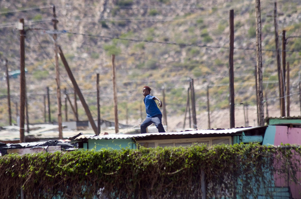 . A young boy throws rocks as Members of the South African Police Services clash with striking farmworkers(not visible), on January 10, 2012 in De Doorns, a small farming town about 140Km North of Cape Town, South Africa. The farm workers have said that they they will not return to work on the fruit growing region\'s farms until they receive a daily wage of at least R150($17) per day, which is about double what they currently earn. AFP PHOTO / RODGER  BOSCH/AFP/Getty Images