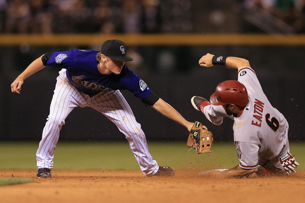 . DENVER, CO - SEPTEMBER 21:  Adam Eaton #6 of the Arizona Diamondbacks slides around the tag of second baseman Josh Rutledge #14 of the Colorado Rockies for a stolen base in the ninth inning at Coors Field on September 21, 2013 in Denver, Colorado.  (Photo by Doug Pensinger/Getty Images)