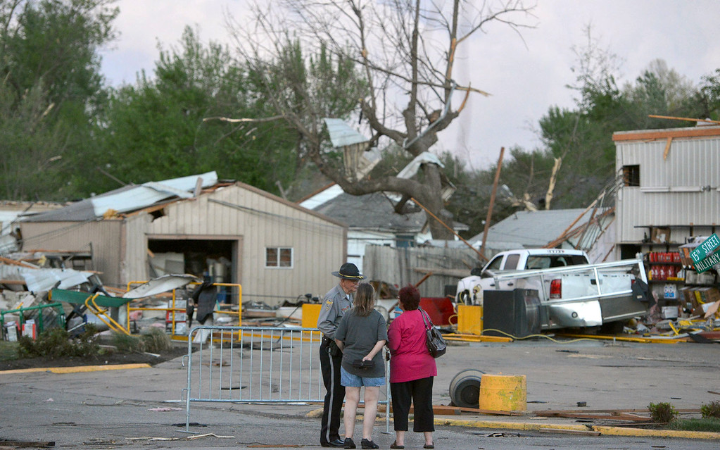 . A officer talks to people at 15th and Military following Sunday\'s tornado in Baxter Springs, Kan., Sunday April 27, 2014.  A powerful storm system rumbled through the central and southern United States on Sunday, spawning a massive tornado that  carved through Little Rock\'s northern suburbs and another that hit Oklahoma and Kansas. (AP Photo/The Joplin Globe, Roger Nomer )