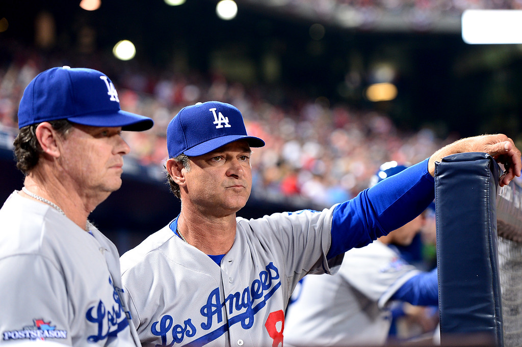 . Los Angeles Dodgers\' pitching coach Rick Honeycutt  and manager Don Mattingly keep their eyes on the eighth inning during game 2 of the playoffs Thursday, October 4, 2013 at Turner Field in Atlanta, Georgia. Braves defeated the Dodger 4-3. (Photo by Sarah Reingewirtz/Pasadena Star- News)
