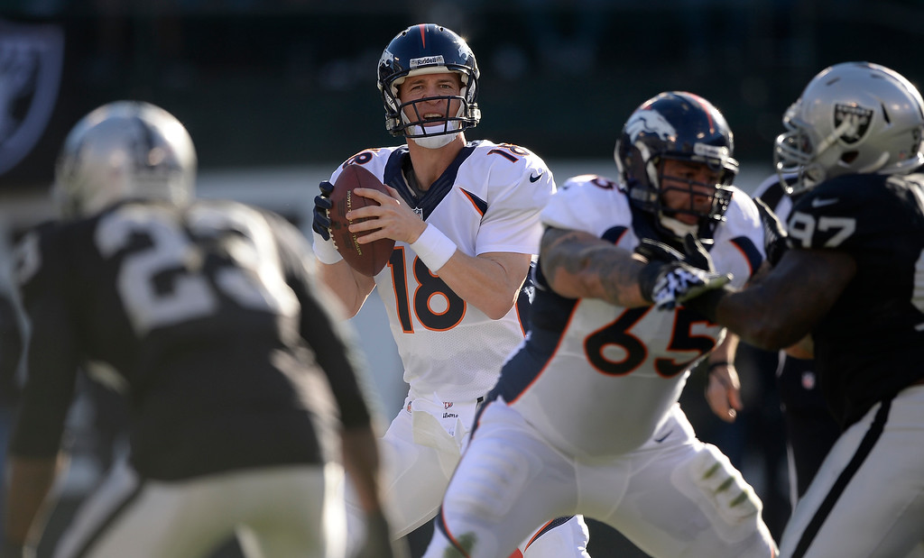 . Denver Broncos quarterback Peyton Manning (18) looks down field t pass against the Oakland Raiders defense during the first quarter at O.co Coliseum. (Photo by John Leyba/The Denver Post)