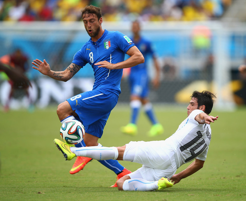 . Nicolas Lodeiro of Uruguay tackles Claudio Marchisio of Italy during the 2014 FIFA World Cup Brazil Group D match between Italy and Uruguay at Estadio das Dunas on June 24, 2014 in Natal, Brazil.  (Photo by Clive Rose/Getty Images)