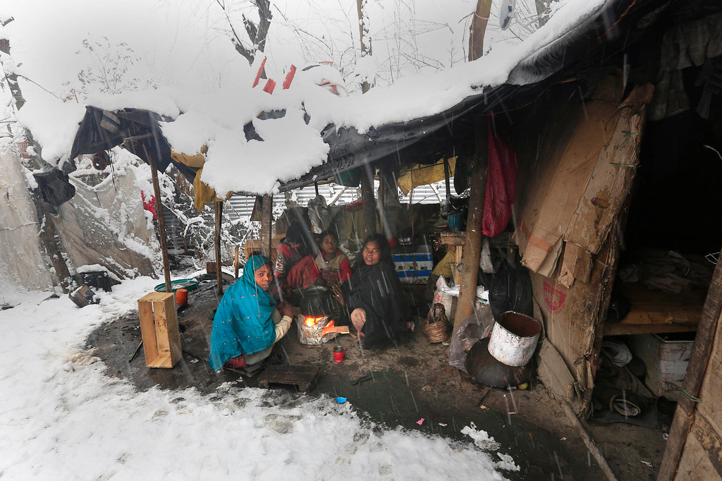 . An Indian family warms themselves near a bonfire outside their temporary shed during a snowfall in Srinagar, India, Tuesday, Dec. 31, 2013. Snowfalls in the Indian portion of Kashmir has disrupted power supply, air traffic and road traffic between Srinagar and Jammu, the summer and winter capitals of India\'s Jammu-Kashmir state, according to news reports. (AP Photo/Dar Yasin)
