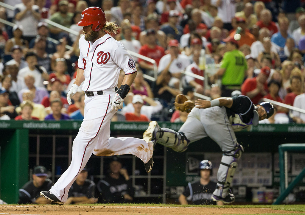 . Colorado Rockies catcher Wilin Rosario, right, watches as Washington Nationals Jayson Werth scores on a wild pitch by pitcher Chad Bettis during the fourth inning of a baseball game at Nationals Park, on Tuesday, July 1, 2014, in Washington. (AP Photo/Evan Vucci)