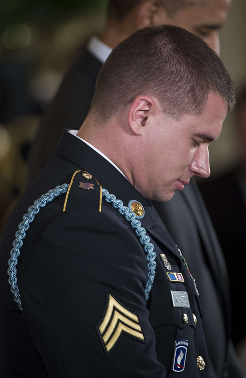 . US Army Sergeant Kyle J. White bows his head for a prayer during a Medal of Honor ceremony in the East Room of the White House May 13, 2014 in Washington, DC. Obama awarded the medal to former US Army Sergeant Kyle J. White  for his actions in Aranas, Afghanistan in 2007. AFP PHOTO/Brendan  SMIALOWSKI/AFP/Getty Images