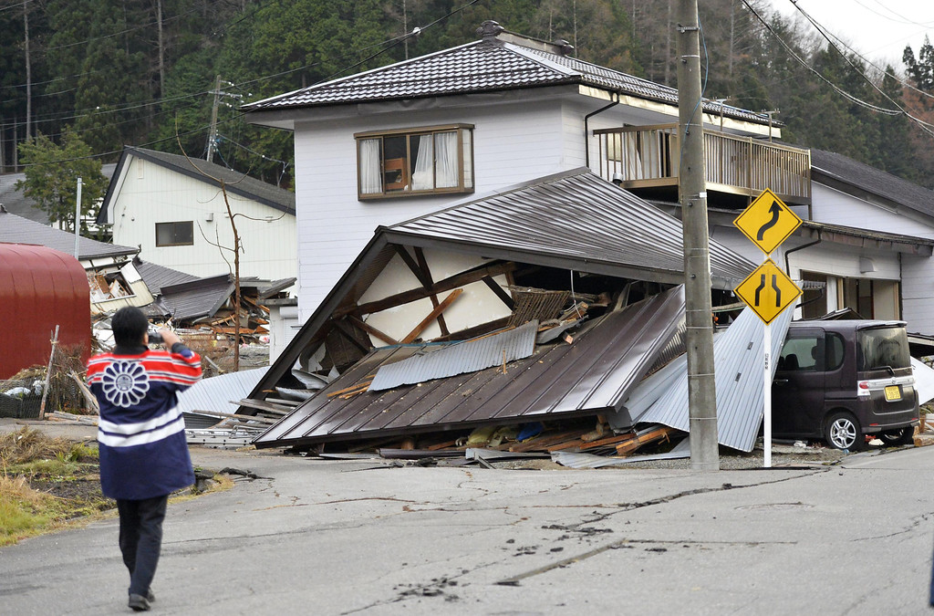 . A man takes a photo of a damaged houses Sunday, Nov. 23, 2014 after a strong earthquake hit Hakuba, Nagano prefecture, central Japan, Saturday night. More than 20 people have been hurt after the magnitude-6.8 earthquake shook the mountainous area that hosted the 1998 winter Olympics. (AP Photo/Kyodo News)