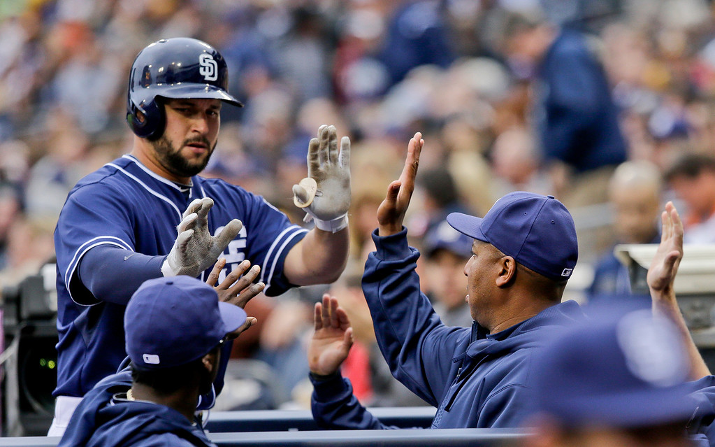 . San Diego Padres\' Yonder Alonso, left, is greeted by teammates after driving in a run with a sacrifice fly against the Colorado Rockies in the first inning of a baseball game on Saturday April 13, 2013, in San Diego. (AP photo/Lenny Ignelzi)