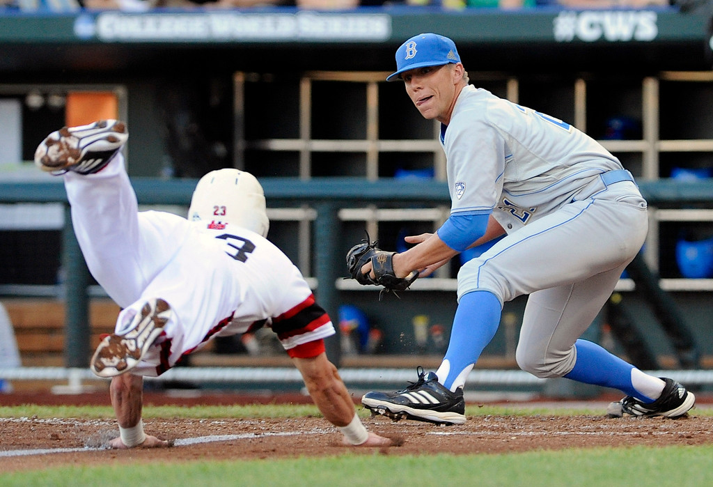 . UCLA pitcher Nick Vander Tuig right, prepares to tag out North Carolina State\'s Jake Armstrong at home plate on a single by Trea Turner in the third inning of an NCAA College World Series baseball game in Omaha, Neb., Tuesday, June 18, 2013. (AP Photo/Eric Francis)