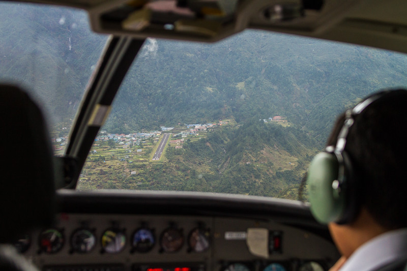 A cockpit view of final approach before landing at Lukla's Tenzing-Hillary Airport as seen through the windshield.